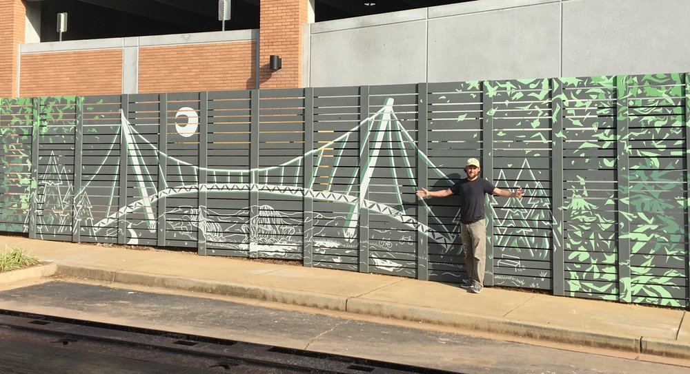 Douglas Piper with his Falls Park mural at 200 East Broad Street